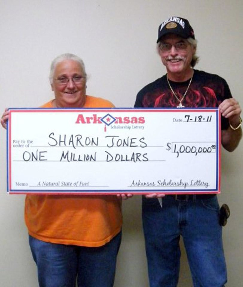 Photo -   This photo provided by the Arkansas Scholarship Lottery shows Sharon Jones, left, and an unidentified man after Jones cashed the winning ticket in 2011. Jones may have to give up the winnings to a woman who threw away the ticket after she bought it, according to a judge's ruling Tuesday. (AP Photo/Arkansas Scholarship Lottery)