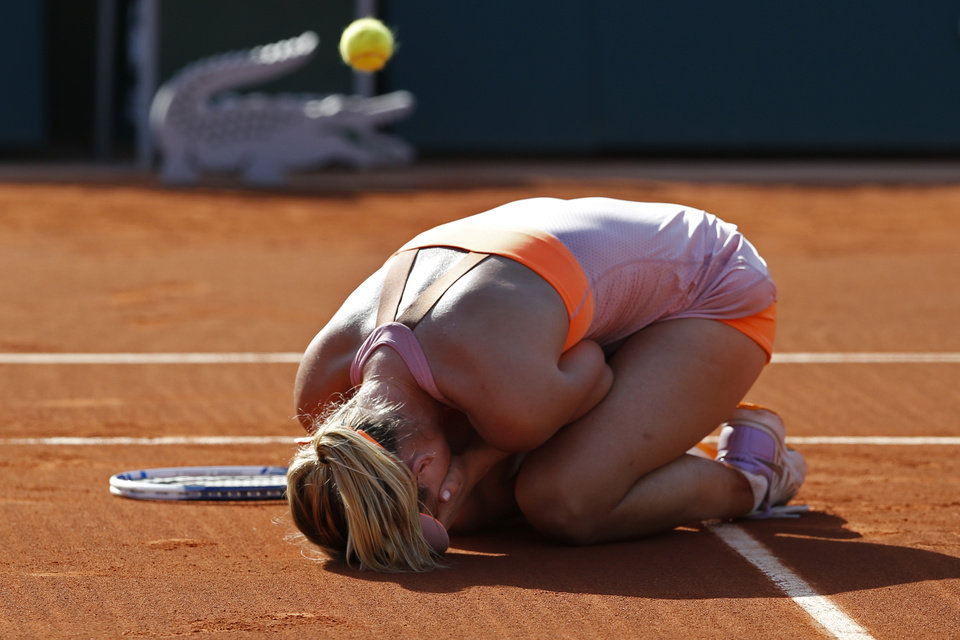 Photo - Russia's Maria Sharapova falls to the ground as the match ball bounces back as she wins the final of the French Open tennis tournament against at the Roland Garros stadium, in Paris, France, Saturday, June 7, 2014. Sharapova won in three sets 6-4, 6-7, 6-4. (AP Photo/Darko Vojinovic)