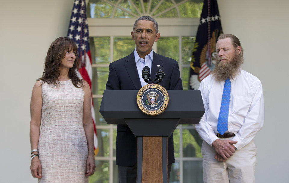 Photo - President Barack Obama speaks with Jani Bergdahl, left, and Bob Bergdahl, right, the parents of U.S. Army Sgt. Bowe Bergdahl, in the Rose Garden of the White House in Washington, Saturday, May 31, 2014, after the announcement that Bowe Bergdahl has been released from captivity. Bergdahl, 28, had been held prisoner by the Taliban since June 30, 2009. He was handed over to U.S. special forces by the Taliban in exchange for the release of five Afghan detainees held by the United States. (AP Photo/Carolyn Kaster)