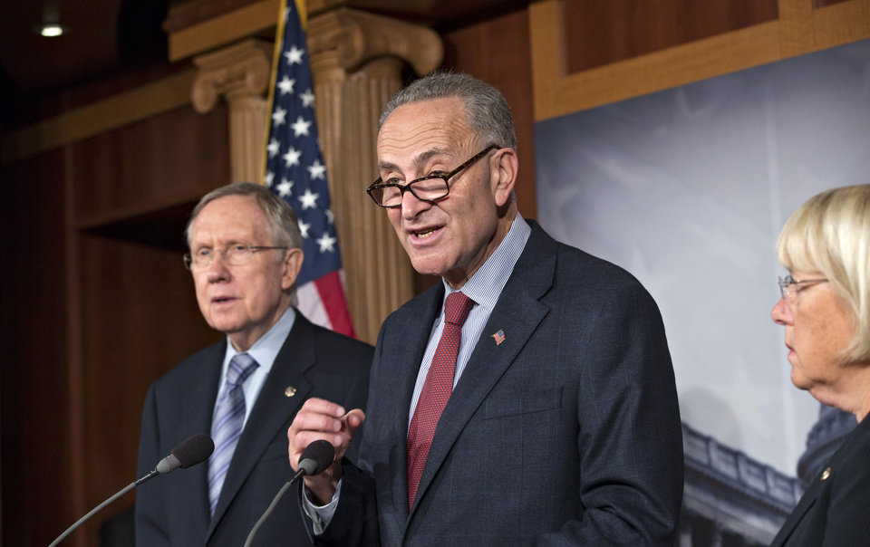 Photo - From left, Senate Majority Leader Harry Reid, D-Nev., Sen. Chuck Schumer, D-N.Y., the Democratic Policy Committee chairman, and Sen. Patty Murray, D-Wash., the Budget Committee chair, repeat their resolve to not touch the Affordable Care Act if House Republicans make rescinding Obamacare a part of a continuing resolution to fund the government, on Capitol Hill in Washington, Thursday, Sept. 19, 2013. (AP Photo/J. Scott Applewhite)