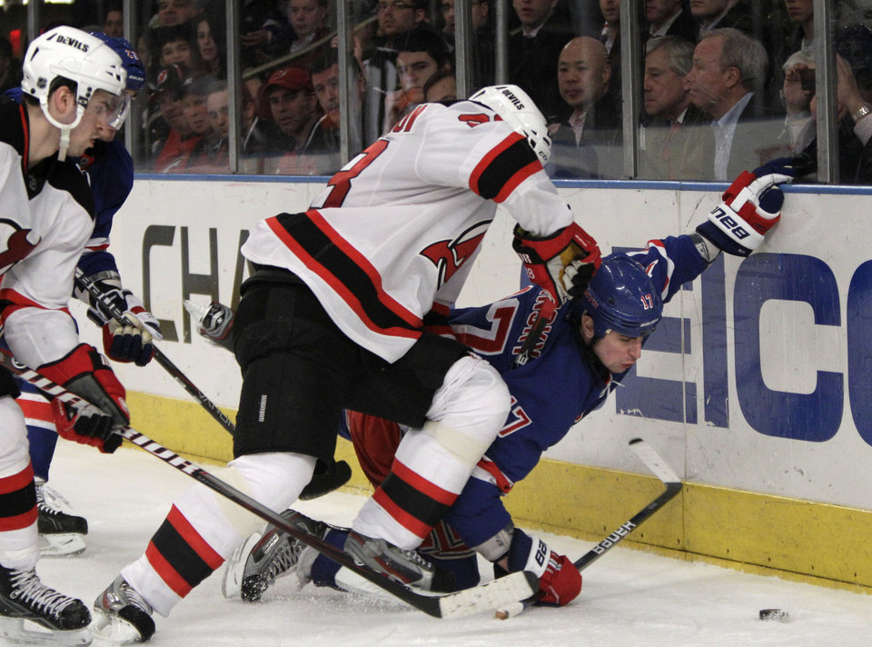 Photo -   New Jersey Devils defenseman Anton Volchenkov, center, pins New York Rangers left wing Brandon Dubinsky (17) to the ice in the second period of their NHL hockey game at Madison Square Garden in New York, Monday, Feb. 27, 2012. (AP Photo/Kathy Willens)