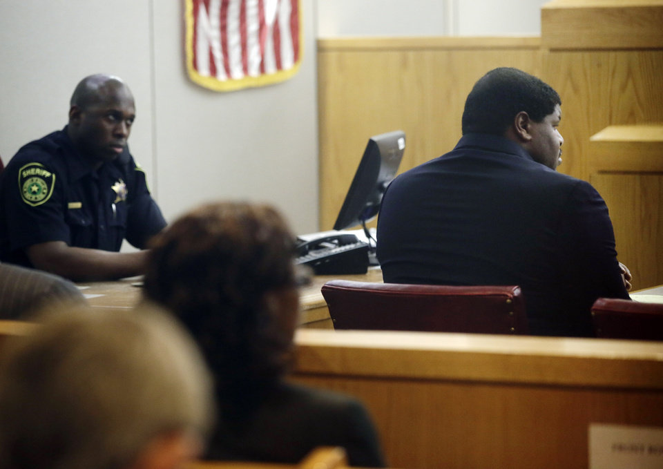 Photo - Former Dallas Cowboy NFL football player Josh Brent, right, sits in court during his trial for intoxication manslaughter, Friday, Jan. 17, 2014, in Dallas. Brent is accused of driving drunk at the time of a December 2012 crash that killed Cowboys practice squad player Jerry Brown. (AP Photo/Tony Gutierrez)