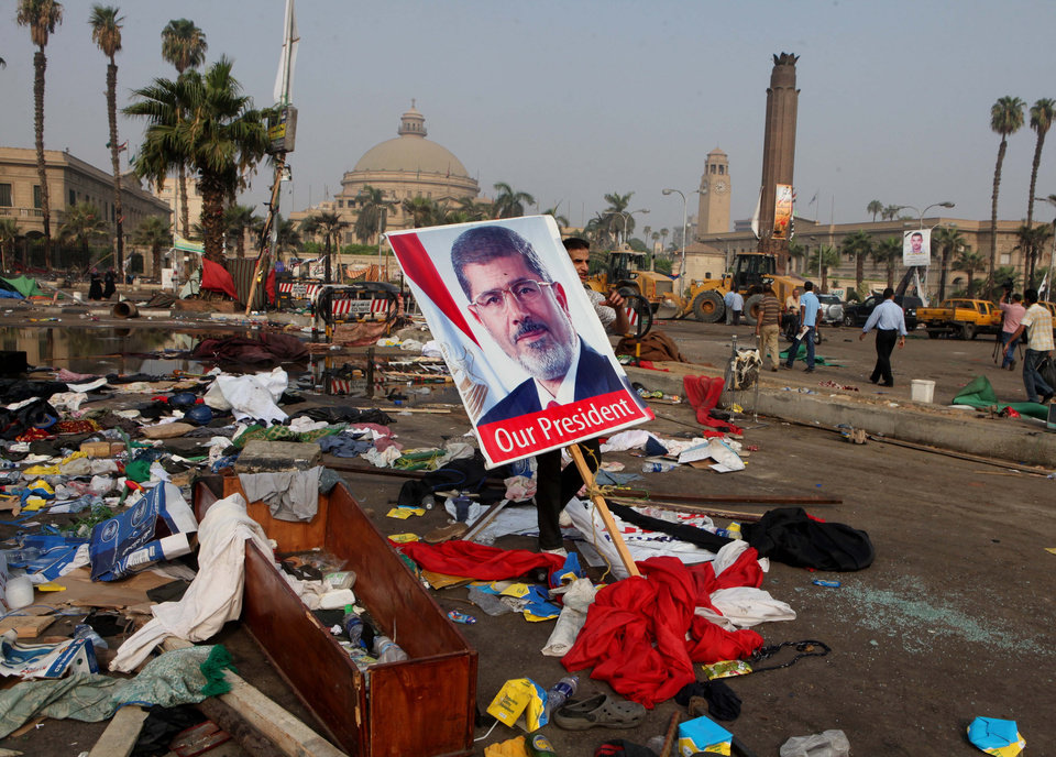 Photo - An Egyptian carries a poster of Egypt's ousted President Mohammed Morsi among debris from a protest camp in Nahda Square, Giza, Cairo, Egypt, Thursday, Aug. 15, 2013. Egypt faced a new phase of uncertainty on Thursday after the bloodiest day since its Arab Spring began, with over 300 people reported killed and thousands injured as police smashed two protest camps of supporters of the deposed Islamist president. Wednesday's raids touched off day-long street violence that prompted the military-backed interim leaders to impose a state of emergency and curfew, and drew widespread condemnation from the Muslim world and the West, including the United States. (AP Photo/Amr Nabil)