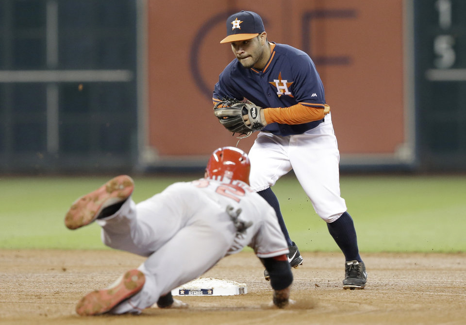 Photo - Houston Astros second baseman Jose Altuve, top, and Los Angeles Angels' Josh Hamilton (32) race for second base on a force-out in the fourth inning of a baseball game on Sunday, April 6, 2014, in Houston. (AP Photo/Pat Sullivan)