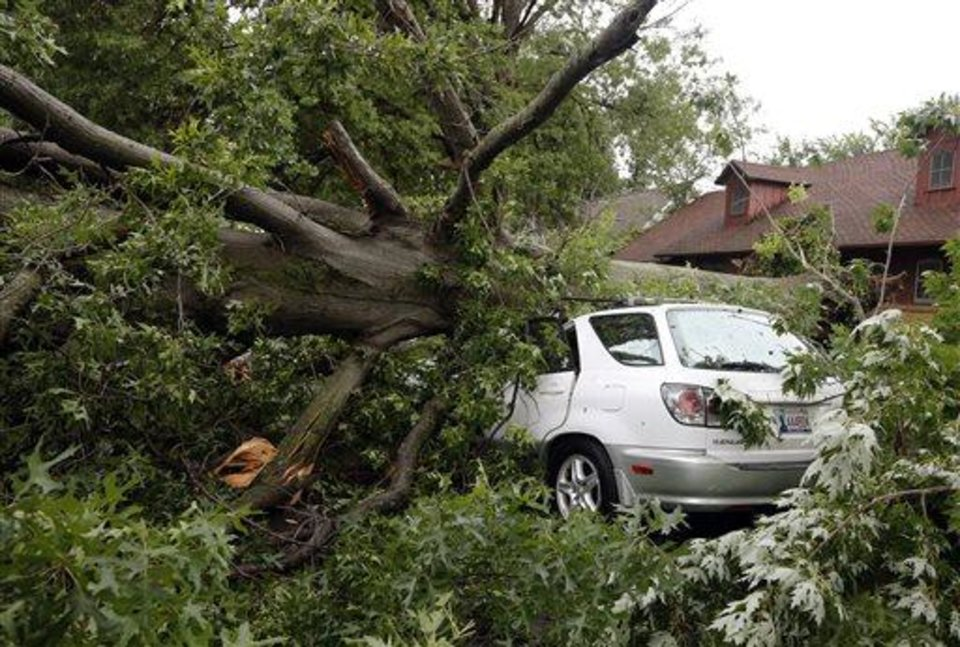 Photo - A car is crushed by an uprooted tree after strong winds hit the area Wednesday, July 24. 2013, in Tulsa, Okla.  Powerful thunderstorms swept through parts of Oklahoma late Tuesday and early Wednesday, knocking out power to tens of thousands of homes and businesses and setting off fires caused by lightning strikes. (AP Photo/Tulsa World,  Tom Gilbert) after strong winds hit the area Wednesday, July 24. 2013, in Tulsa, Okla.  Powerful thunderstorms swept through parts of Oklahoma late Tuesday and early Wednesday, knocking out power to tens of thousands of homes and businesses and setting off fires caused by lightning strikes. (AP Photo/Tulsa World,  Tom Gilbert)
