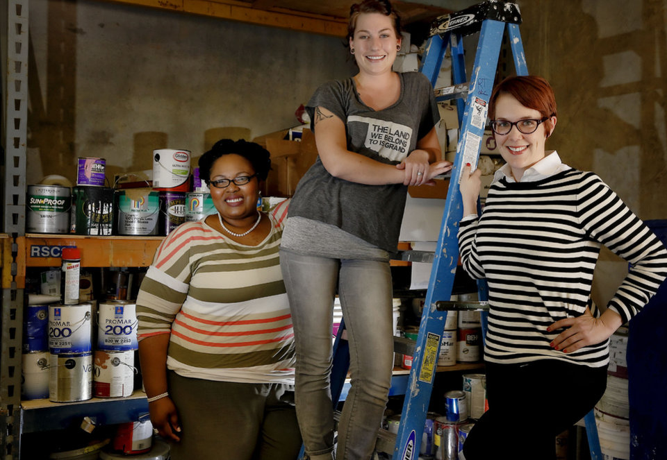 Photo - Neighborhood Alliance of Oklahoma City and Rebuilding Together members, from left, Ashley Dickson, Madeline Whitehorn and Jennifer Thurman pose with donated paint that will be used to spruce up a neighborhood this summer. Photo by Chris Landsberger, The Oklahoman  CHRIS LANDSBERGER - CHRIS LANDSBERGER