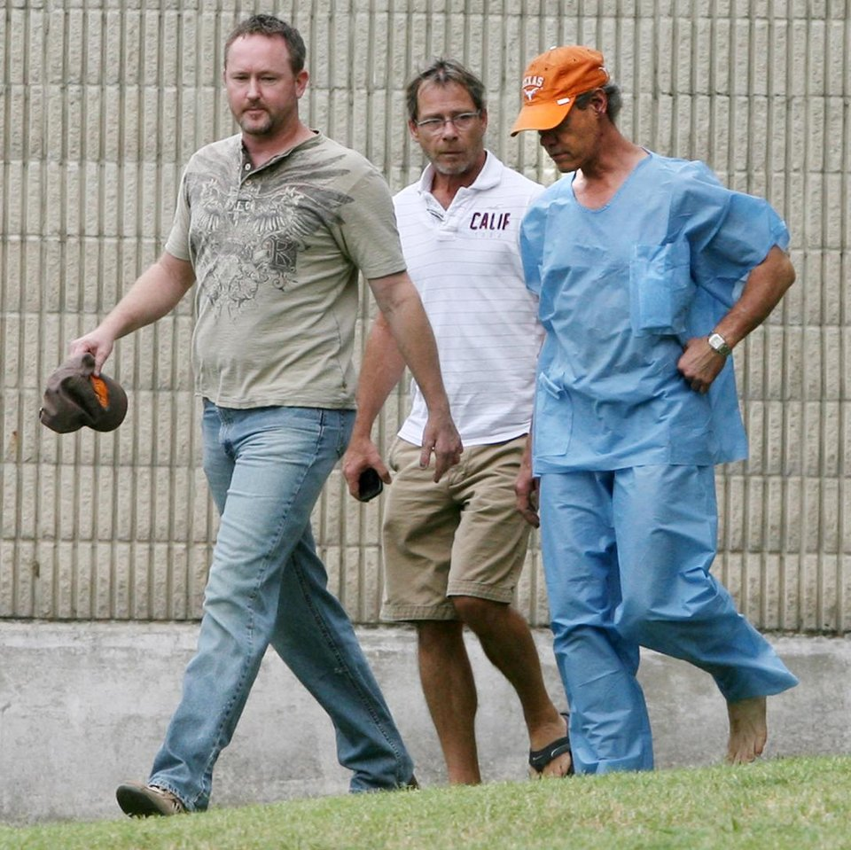 Photo -   Randy Travis, far right exits the Grayson County jail with two unknown persons Wednesday Aug. 8, 2012, in Sherman, Texas, after being arraigned on charges of driving while intoxicated and retaliation. (AP Photo/The Herald Democrat, Chris Jennings) NO MAGS, NO SALES
