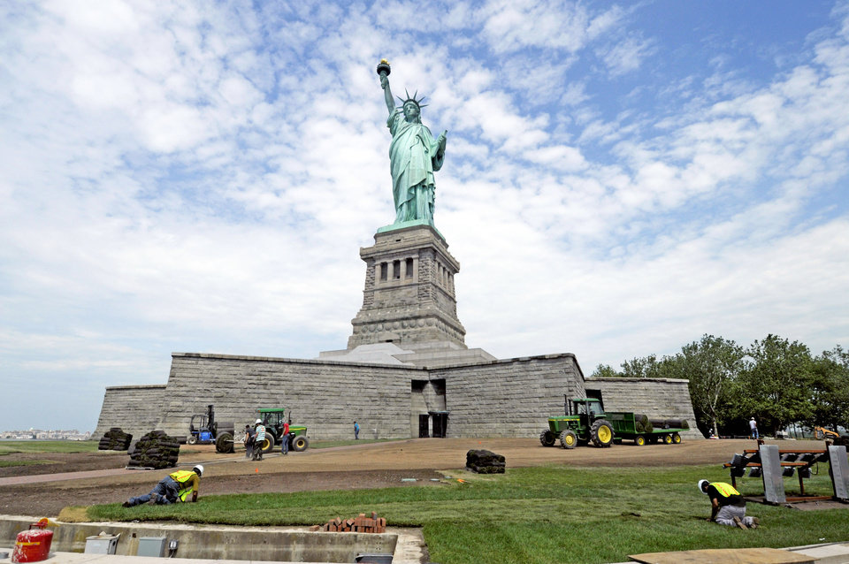 Photo - In this June 26, 2013 photo provided by the National Park Service, workers on Liberty Island install sod around the national monument which is set to re-open on the 4th of July, in New York. Months after railings broke, docks and paving stones were torn up and buildings were flooded by Superstorm Sandy, the Statue of Liberty will finally welcome visitors again. (AP Photo/National Park Service,