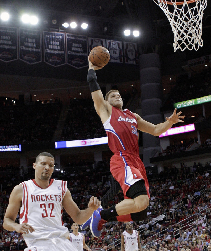 Photo - Los Angeles Clippers forward Blake Griffin (32) drives for a dunk past Houston Rockets guard Francisco Garcia (32) during the first half of an NBA basketball game Saturday, March 30, 2013, in Houston. (AP Photo/Bob Levey)