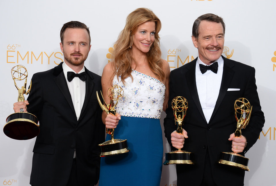 "Photo - Aaron Paul, left, poses with the award for outstanding supporting actor in a drama series, with Anna Gunn, center, with the award for outstanding supporting actress in a drama series, and Bryan Cranston with the awards for outstanding lead actor in a drama series and outstanding drama series for ""Breaking Bad"" in the press room at the 66th Annual Primetime Emmy Awards at the Nokia Theatre L.A. Live on Monday, Aug. 25, 2014, in Los Angeles. (Photo by Jordan Strauss/Invision/AP)"