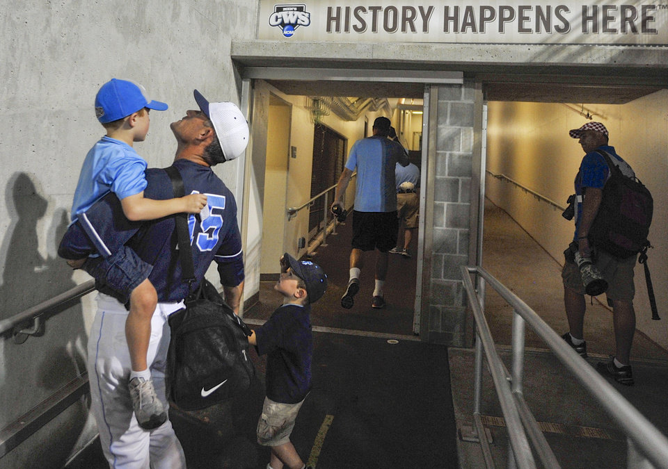 Photo - North Carolina assistant coach Scott Jackson and his sons Ryan, left, and Tyler, walks away from the playing field at TD Ameritrade Park after losing 4-1 to UCLA in an NCAA College World Series baseball game in Omaha, Neb., Friday, June 21, 2013. (AP Photo/Eric Francis)