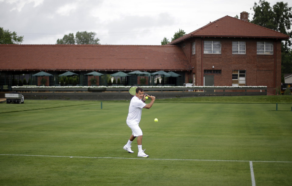 Photo - Armand Molino plays tennis at the Wessen Lawn Tennis Club in Pontiac, Mich., Tuesday, June 24, 2014. The club's owner is hoping to impress the ATP Tour enough to bring a tournament to the site in a couple years. Bill Massie says he has spent $1.5 million to build 24 outdoor grass courts, adding he has plans to add seven hard and three clay courts in the future. (AP Photo/Paul Sancya)