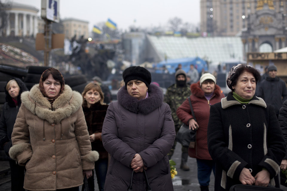 Photo - People attend a funeral ceremony for Andryi Pozniak, 25,a self defense volunteer who was shot and killed by an unknown assailant two days ago near Kiev's Independence Square, Ukraine, Thursday, March 6, 2014. (AP Photo/David Azia)