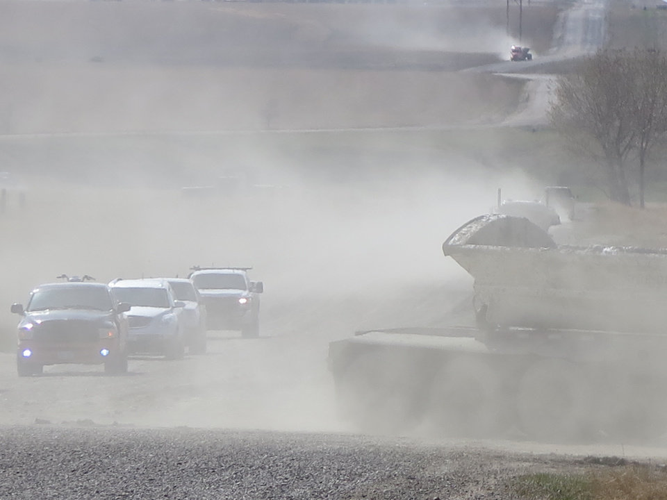 Photo - Vehicles drive through dust on a gravel road in Williston, N.D., Saturday, May 3, 2014. Unpaved roads are essential to North Dakota's oil industry, but controlling the dust they produce can be difficult and expensive. (AP Photo/Josh Wood)