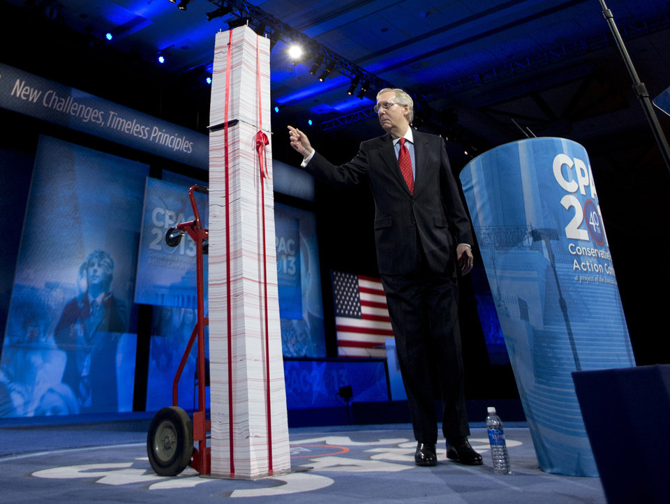 FILE - In this March 15, 2013, file photo the Senate Minority Leader, Republican Mitch McConnell of Kentucky, points to a 7-foot stack of �Obamacare� regulations to underscore his disdain during the 40th annual Conservative Political Action Conference in National Harbor, Md.  McConnell said Democrats have been predicting for years that Americans would learn to love the health care overhaul and that has not happened. �I agree that it will be a big issue in 2014,� he said. �I think it will be an albatross around the neck of every Democrat who voted for it. They are going to be running away from it, not toward it.� (AP Photo/Manuel Balce Ceneta, File)