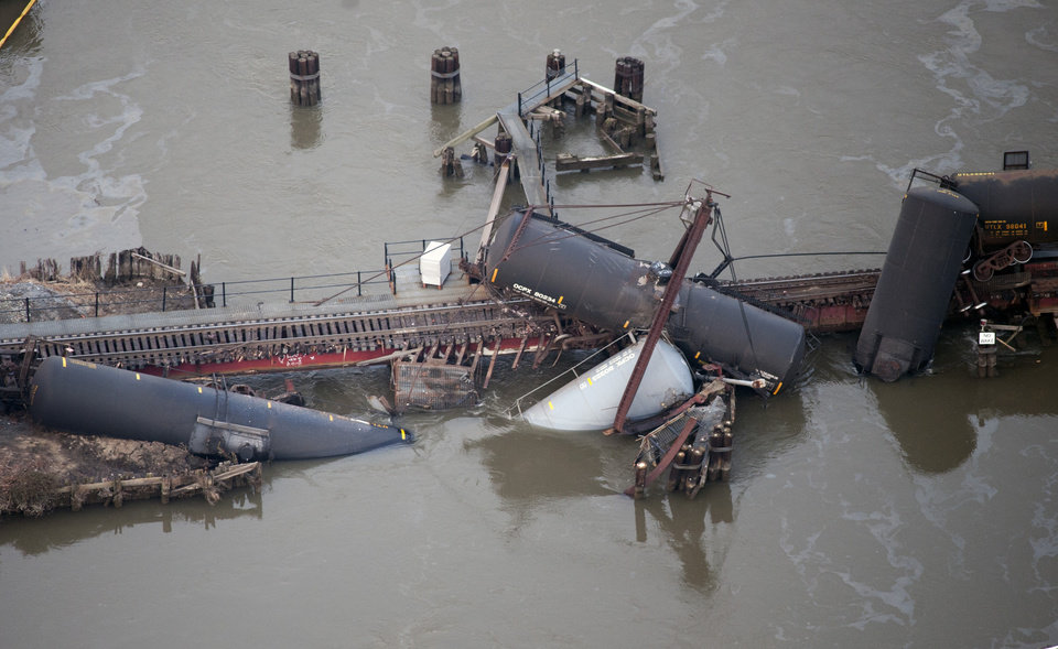 Photo - Several cars lay in the water after a freight train derailed in Paulsboro, N.J., Friday, Nov. 30, 2012. People in three southern New Jersey towns were told Friday to stay inside after the freight train derailed and several tanker cars carrying hazardous materials toppled from a bridge and into a creek. (AP Photo/Cliff Owen)