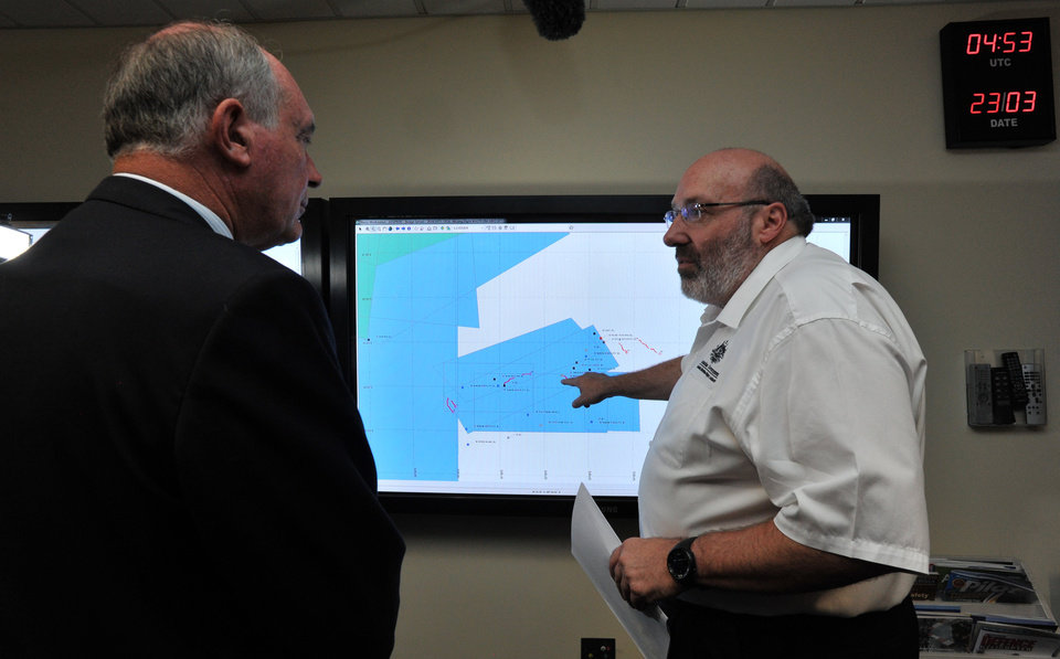 Photo - Mike Barton, rescue coordination chief, right, shows Australia's Deputy Prime Minister, Warren Truss, the map of the Indian Ocean search areas at the rescue coordination center of Australian Maritime Safety Authority in Canberra, Sunday, March 23, 2014. Planes and ships scrambled Sunday to find a pallet and other debris in a remote patch of the southern Indian Ocean to determine whether the objects were from the Malaysia Airlines jet that has been missing for more than two weeks. (AP Photo/Graham Tidy, Pool)