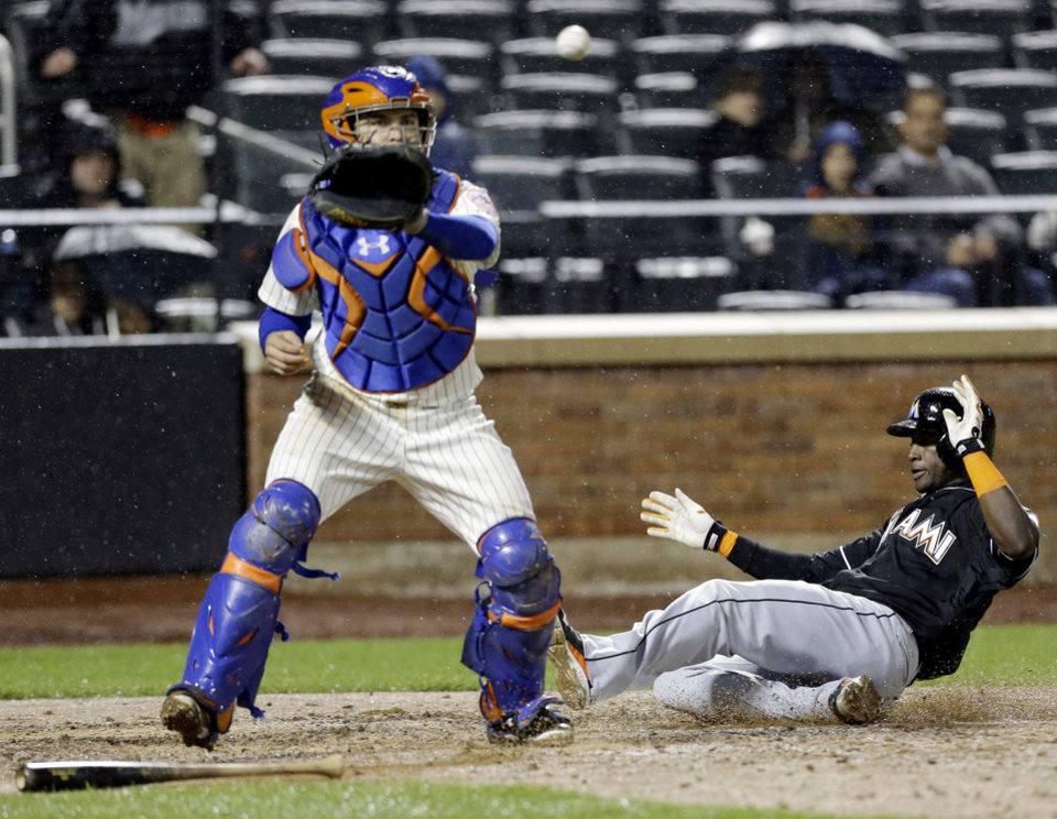 Photo - Miami Marlins' Adeiny Hechavarria, right, slides past New York Mets catcher Travis d'Arnaud on a Reed Johnson double during the sixth inning of a baseball game, Saturday, April 26, 2014, in New York. (AP Photo/Frank Franklin II)