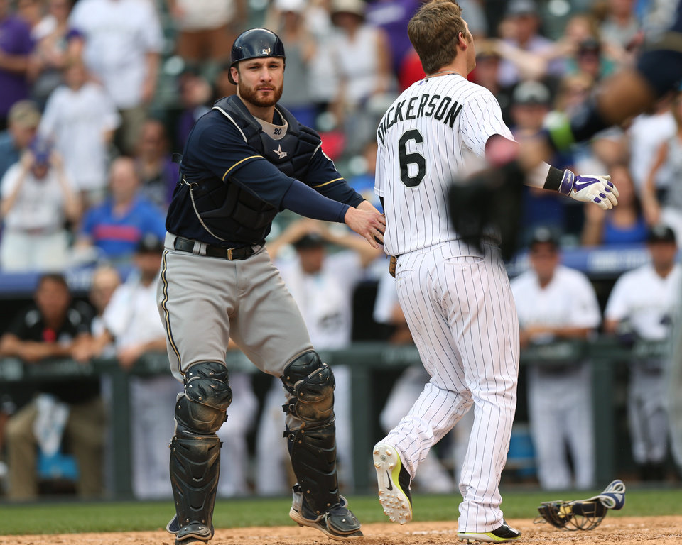 Photo - At home plate, Milwaukee Brewers catcher Jonathan Lucroy, left, tags out Colorado Rockies' Corey Dickerson who was trying to stretch a triple into an inside-the-park home run in the ninth inning of the Brewers' 6-5 victory in a baseball game in Denver, Sunday, June 22, 2014. (AP Photo/David Zalubowski)