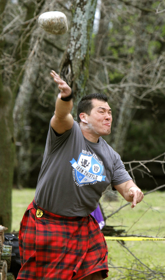 Photo - Gary Robertson competes in the stone put event during the Iron Thistle Scottish Heritage Festival on Saturday.  Photo By Paul Hellstern, The Oklahoman  PAUL HELLSTERN - Oklahoman