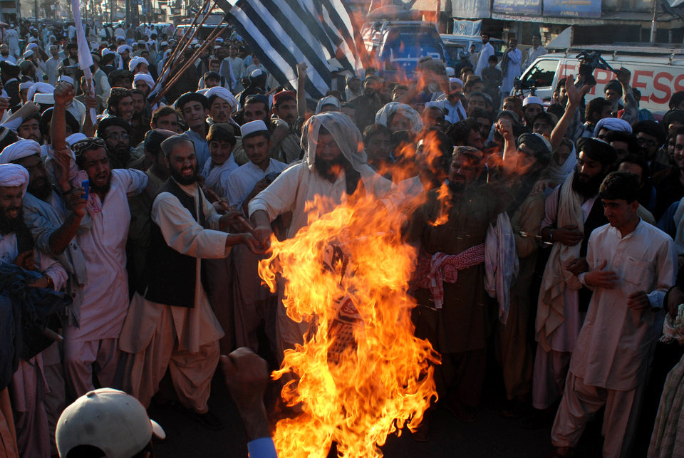 Photo - Angry supporters of Pakistani religious party Jamiat Ulema-e-Islam burn representation of the United States during a rally to condemn the killing of Osama bin Laden in Quetta, Pakistan on Monday, May 2, 2011.  al-Qaida chief  Osama bin Laden was slain in his hideout in Pakistan early Monday in a firefight with U.S. forces, ending a manhunt that spanned a decade. (AP Photo/Arshad Butt)(AP Photo/Arshad Butt) ORG XMIT: QUT108