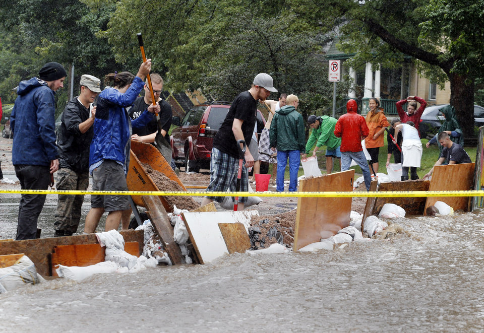 Photo - Residence of an apartment house work to divert flood water from their building in Boulder, Colo., on Thursday, Sept. 12, 2013. Flash flooding in Colorado has cut off access to towns, closed the University of Colorado in Boulder and left at least three people dead. (AP Photo/Ed Andrieski)