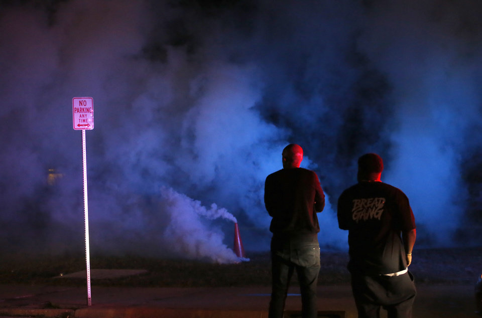 Photo - Protesters stand in front of the Oklahoma City Police Department as a tear gas cloud goes in the air in Oklahoma City, Saturday, May 30, 2020. The protest was in response to the death of George Floyd. [Sarah Phipps/The Oklahoman]