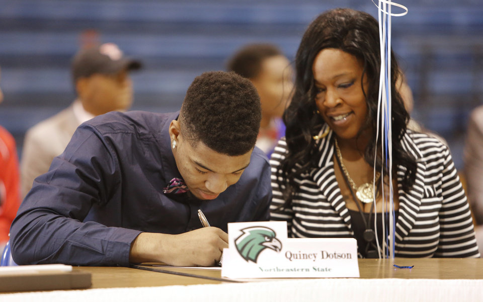 Photo - Millwood's Quincy Dotson signs with Northeastern State with his mother, Tonya Dotson at his side in Oklahoma City, Wednesday February 05, 2014. Photo By Steve Gooch, The Oklahoman