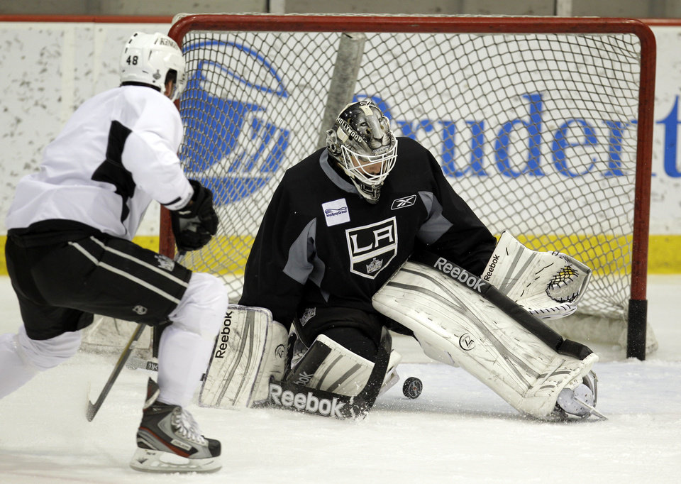 Photo -   Los Angeles Kings goalie Jonathan Bernier, right, tries to block a shot by Andrei Loktionov, of Russia, during practice in preparation for Game 2 of the NHL hockey Stanley Cup Final series against the New Jersey Devils, Thursday, May 31, 2012, in Newark, N.J. (AP Photo/Julio Cortez)