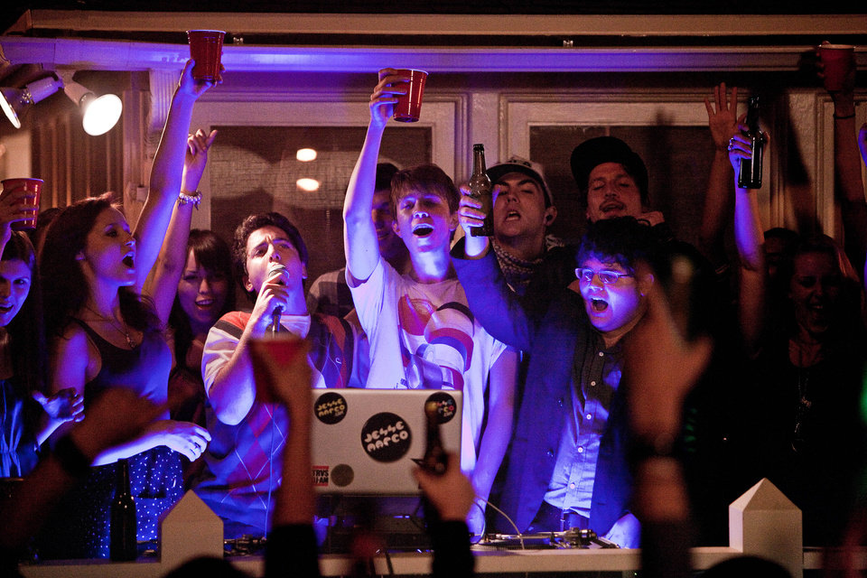 "In this film image released by Warner Bros., from left, Oliver Cooper, with microphone, Thomas Mann and Jonathan Daniel Brown are shown in a scene from ""Project X."" (AP Photo/Warner Bros., Beth Dubber)"