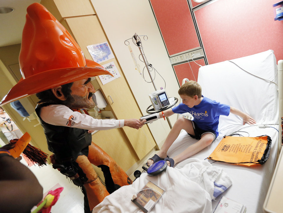 Oklahoma State mascot Pistol Pete shakes the hand of Ernest Cobb, 9, during a visit by OSU football players to The Children's Hospital in Oklahoma City, Wednesday, July 11, 2012. Photo by Nate Billings, The Oklahoman