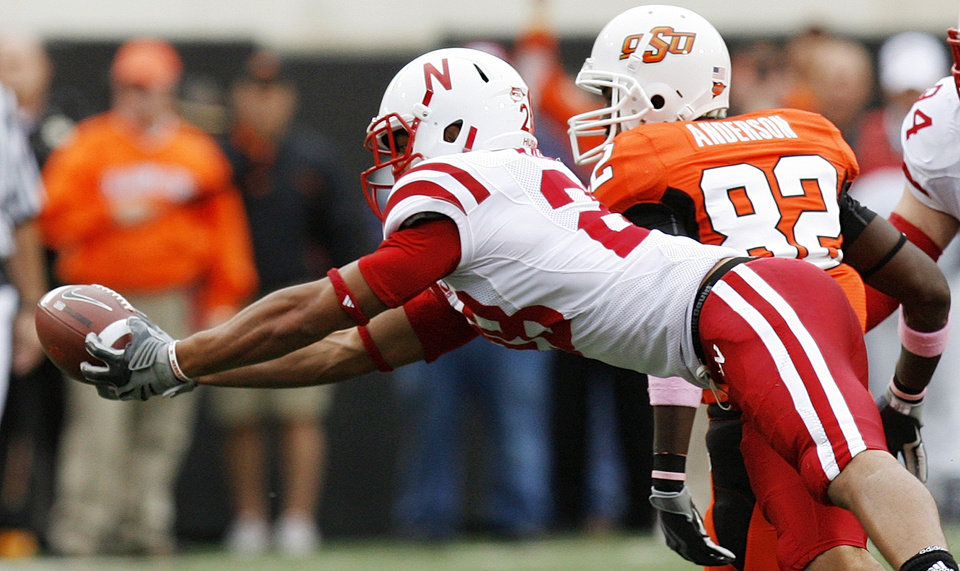 Photo - Nebraska's Eric Hagg (28) intercepts a pass from OSU's Brandon Weeden (not pictured) next to Isaiah Anderson (82) in the second quarter during the college football game between the Oklahoma State Cowboys (OSU) and the Nebraska Huskers (NU) at Boone Pickens Stadium in Stillwater, Okla., Saturday, Oct. 23, 2010. Photo by Nate Billings, The Oklahoman