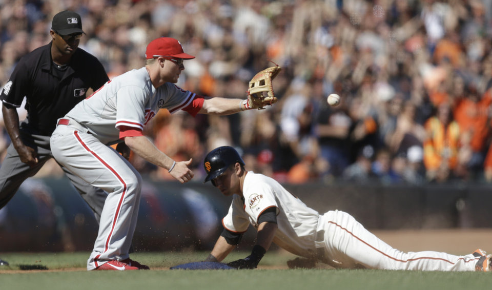 Photo - San Francisco Giants' Joe Panik, right, slides safe beneath the ball and Philadelphia Phillies third baseman Cody Asche in the eighth inning of a baseball game Saturday, Aug. 16, 2014, in San Francisco. (AP Photo/Ben Margot)
