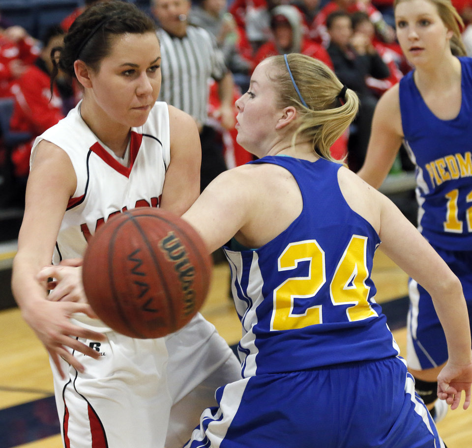 Photo - McLoud's Ashley Boyer (12) passes the ball past Peidmont's Abbie Hall (24) during a basketball tournament at the Kingfisher High School gym on Thursday, Jan. 24, 2013, in Kingfisher, Okla.  Photo by Chris Landsberger, The Oklahoman