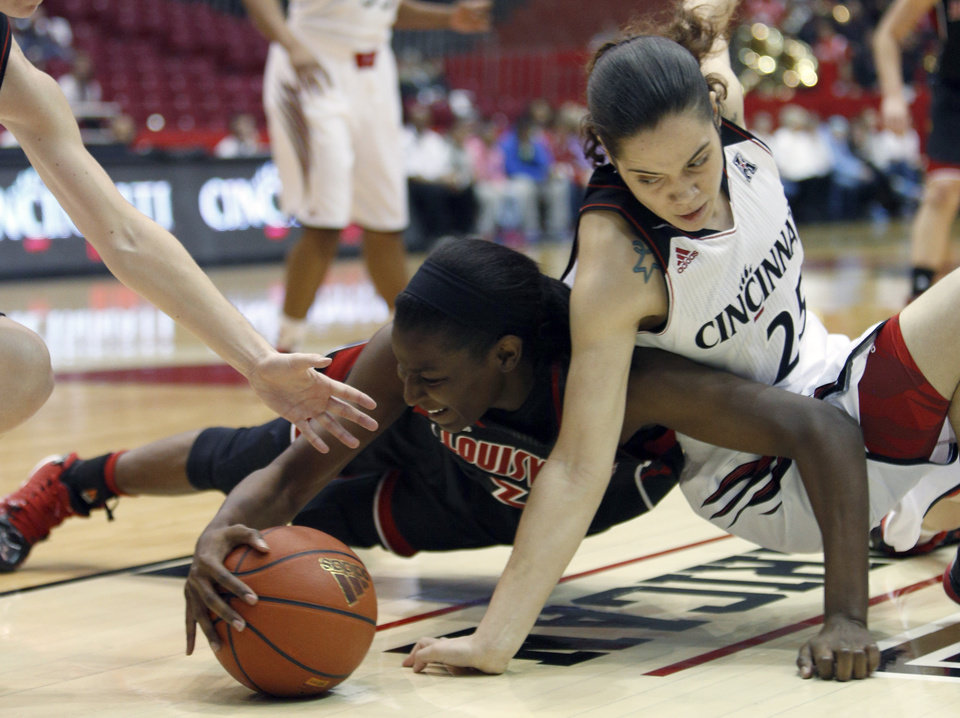 Photo - Louisville forward Asia Taylor (31) goes for the ball against Cincinnati guard Chelsea Jamison (25) during the first half of an NCAA college basketball game, Saturday, March 1, 2014, in Cincinnati. (AP Photo/David Kohl)