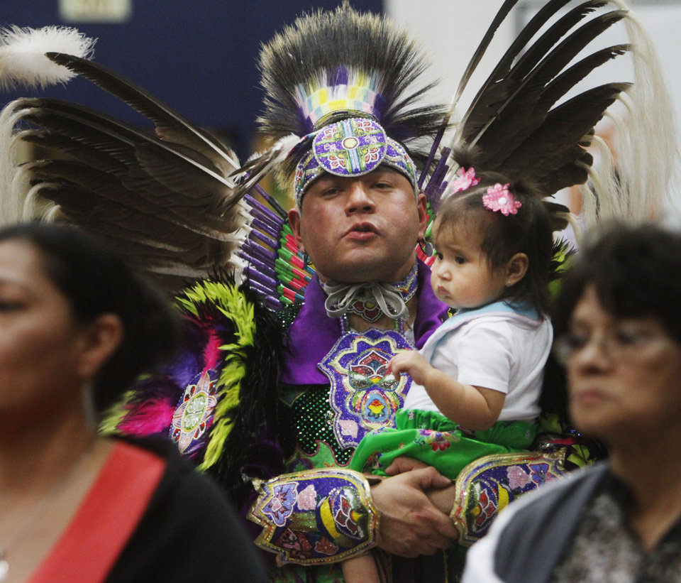 Photo -  Cecil Gray, of Oklahoma City, holds his 1-year-old daughter Glory Gray as he dances at the University of Central Oklahoma powwow. Photo by K.T. King, The Oklahoman   KT King -