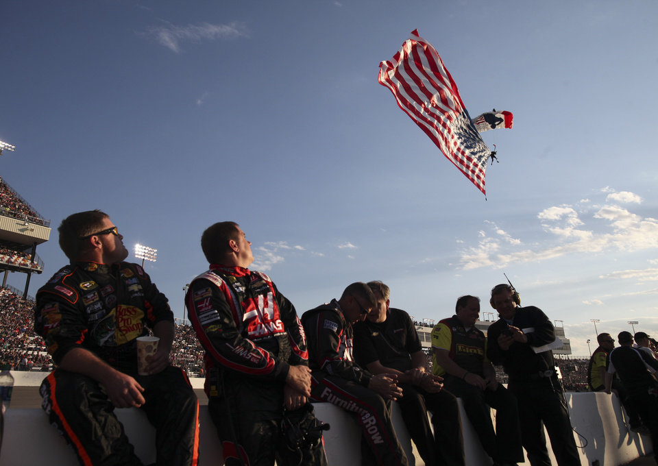 Photo - Members of a pit crew watch a parachutist as he comes down with a U.S. flag before the NASCAR Sprint Cup auto race at Richmond International Raceway in Richmond, Va., Saturday, April 26, 2014. (AP Photo/Zach Gibson)