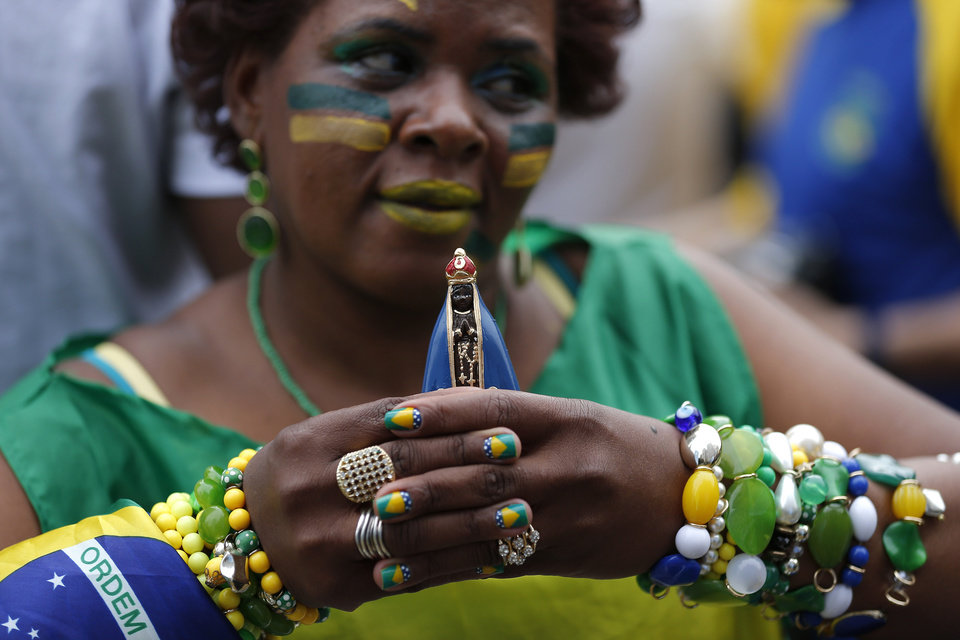 Photo - A Brazilian soccer fan decked in her team's colors, holds holds a small statue of Brazil's patron saint, Our Lady of Aparecida, as she waits for the start of the World Cup semifinal match between Brazil and Germany, in the FIFA Fan Fest area, in Sao Paulo, Brazil, Tuesday, July 8, 2014. (AP Photo/Dario Lopez-Mills)