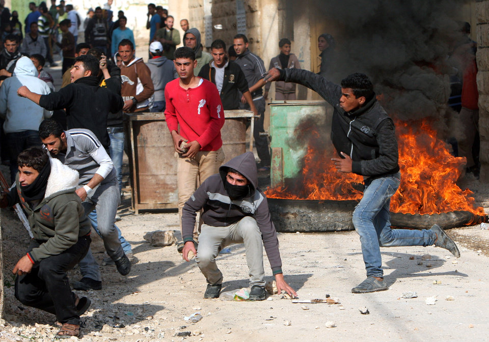 Palestinians hurl stones at Israeli soldiers, not seen, during clashes in the West Bank village of Tamoun, near Jenin, Tuesday, Jan. 1, 2013. Palestinians say a raid by Israeli soldiers disguised as vegetable vendors to seize members of a militant group has sparked clashes in the northern West Bank. (AP Photo/Mohammed Ballas)