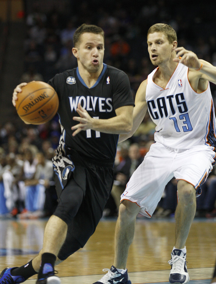 Photo - Minnesota Timberwolves guard Jose Barea, left, drives against Charlotte Bobcats guard Luke Ridnour during the first half of an NBA basketball game in Charlotte, N.C., Friday, March 14, 2014. (AP Photo/Nell Redmond)