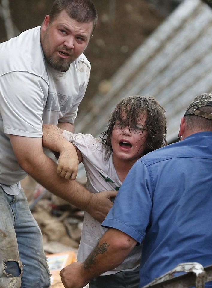 Photo - A child calls to his father after being pulled from the rubble of the Tower Plaza Elementary School following a tornado in Moore, Okla., Monday, May 20, 2013. A tornado as much as half a mile (.8 kilometers) wide with winds up to 200 mph (320 kph) roared through the Oklahoma City suburbs Monday, flattening entire neighborhoods, setting buildings on fire and landing a direct blow on an elementary school. (AP Photo Sue Ogrocki)