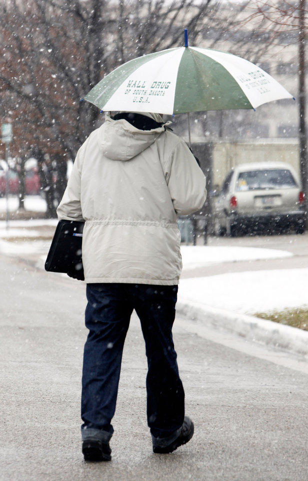 Photo - A pedestrian walks Monday in the falling snow in downtown Oklahoma City. Photo by Paul B. Southerland,  The Oklahoman