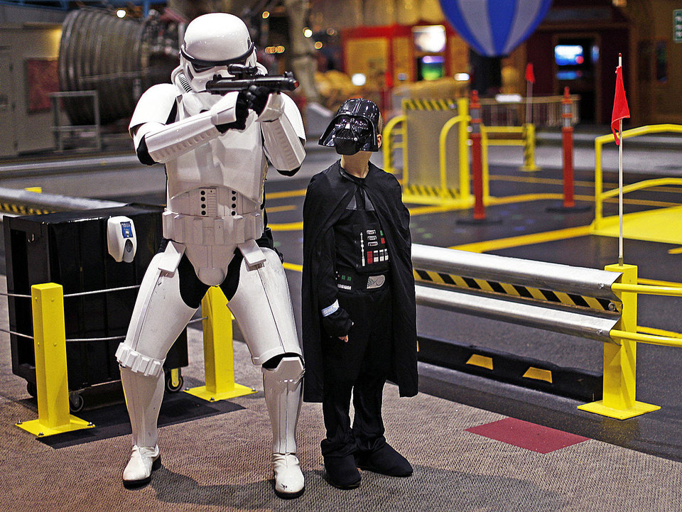 Landon Hood, 9, of Dale, looks up at Mark Elden as they get their photo taken during the Science Museum Oklahoma's Bright Night of Star Wars sleepover.