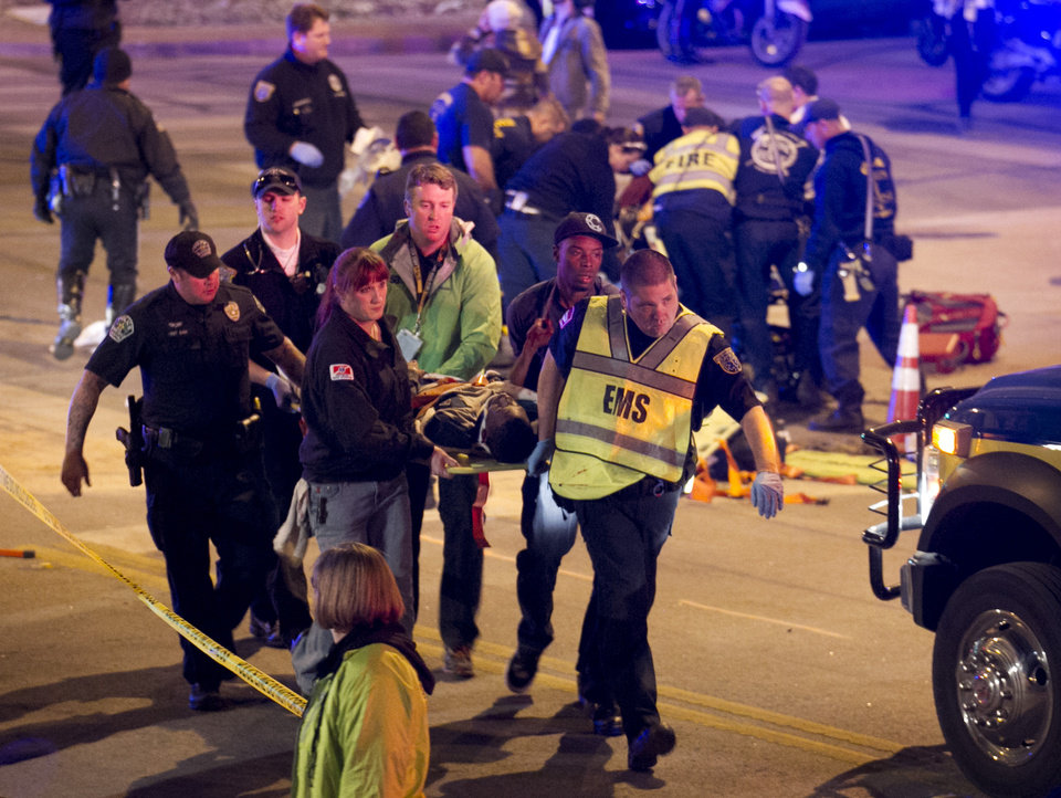 Photo - A patient is carried away after being struck by a vehicle on Red River Street in downtown Austin, Texas, during SXSW on Wednesday March 12, 2014. Police say two people were confirmed dead at the scene after a car drove through temporary barricades set up for the South By Southwest festival and struck a crowd of pedestrians.  (AP Photo/Austin American-Statesman, Jay Janner)