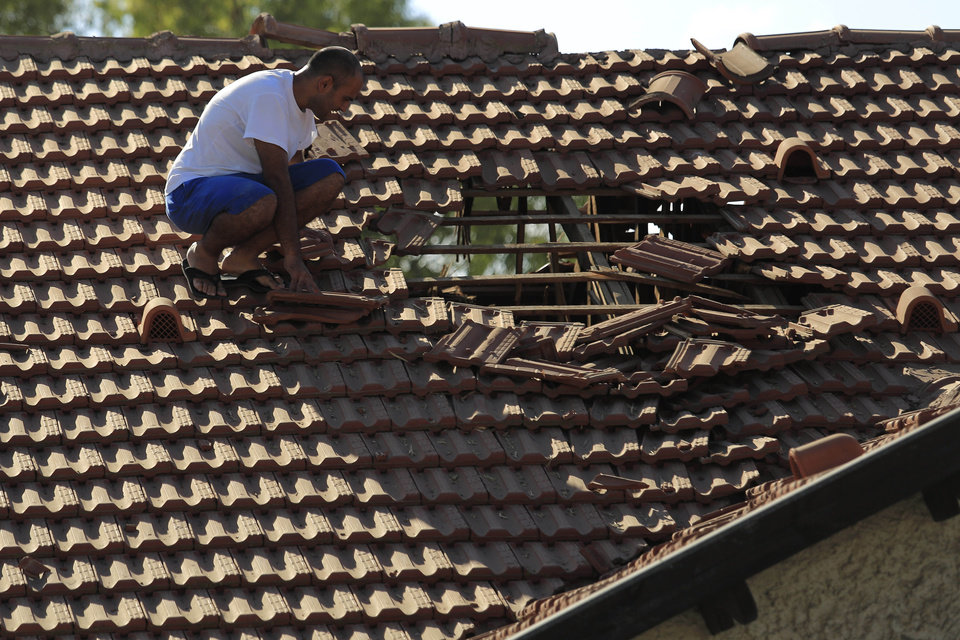 Photo - An Israeli man examines the damage to the roof of his house after a rocket fired from Gaza hit in a residential neighborhood of the southern city of Sderot, Israel, Friday, August 8, 2014. (AP Photo/Tsafrir Abayov)