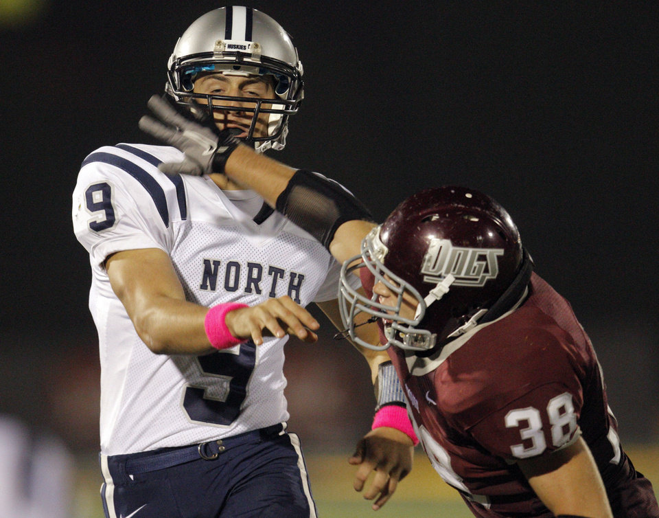 Photo - Edmond Memorial's Chase Thackerson pressures Edmond North's Luke Hoskins during the high school football game between Edmond North and Edmond Memorial at Wantland Stadium in Edmond, Okla., Friday, Sept. 16, 2011. Photo by Sarah Phipps, The Oklahoman