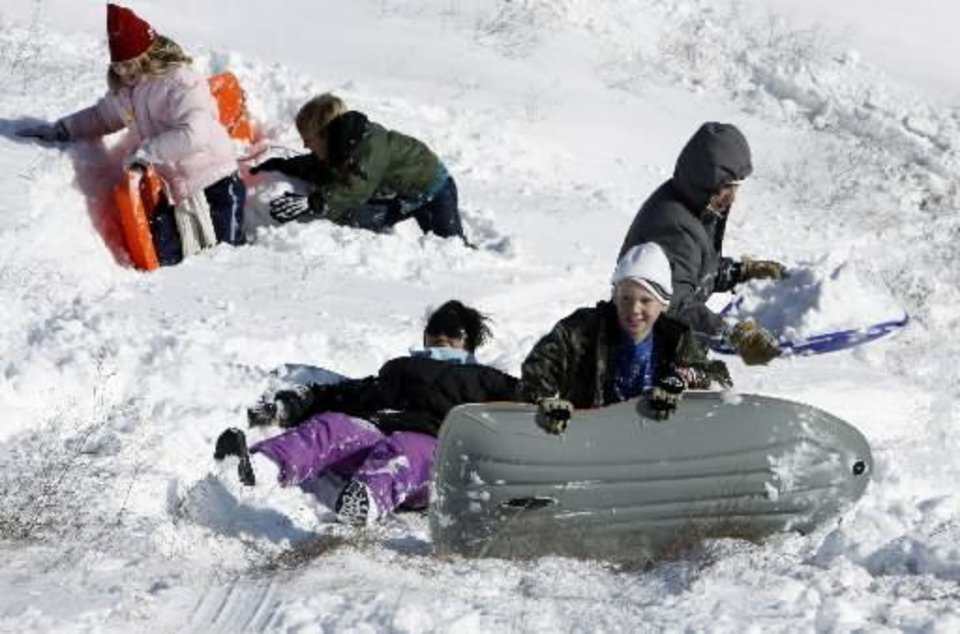 Sledders slide down the embankment on Interstate 35 at Tecumseh Rd. on Christmas Day on Friday, Dec. 25, 2009, in Norman, Okla. after a record snowstorm. Photo by Steve Sisney