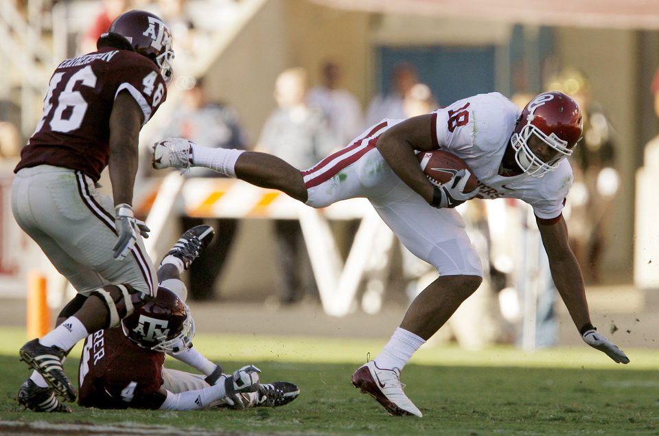 Photo - OU's Jermaine Gresham gets by Matt Featherston , left, and Danny Gorrer of Texas A&M during the college football game between the University of Oklahoma and Texas A&M University at Kyle Field in College Station, Texas, Saturday, November 8, 2008.  BY BRYAN TERRY, THE OKLAHOMAN