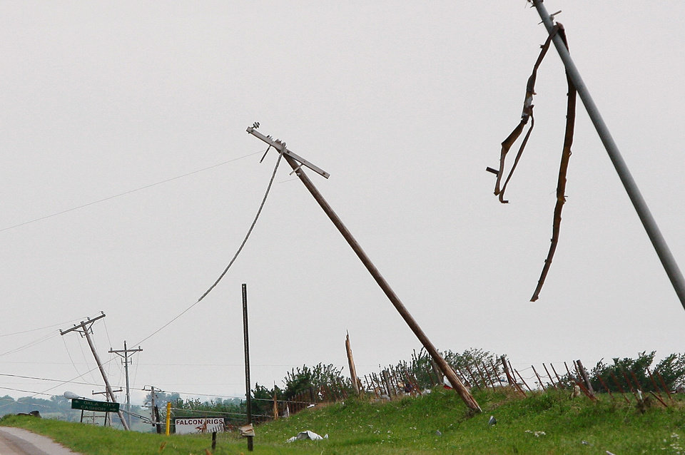 Photo - A tornado pulled down power lines and twisted tall utility poles on SH 74 near Cashion Tuesday afternoon,  May 24, 2011,   Photo by Jim Beckel, The Oklahoman