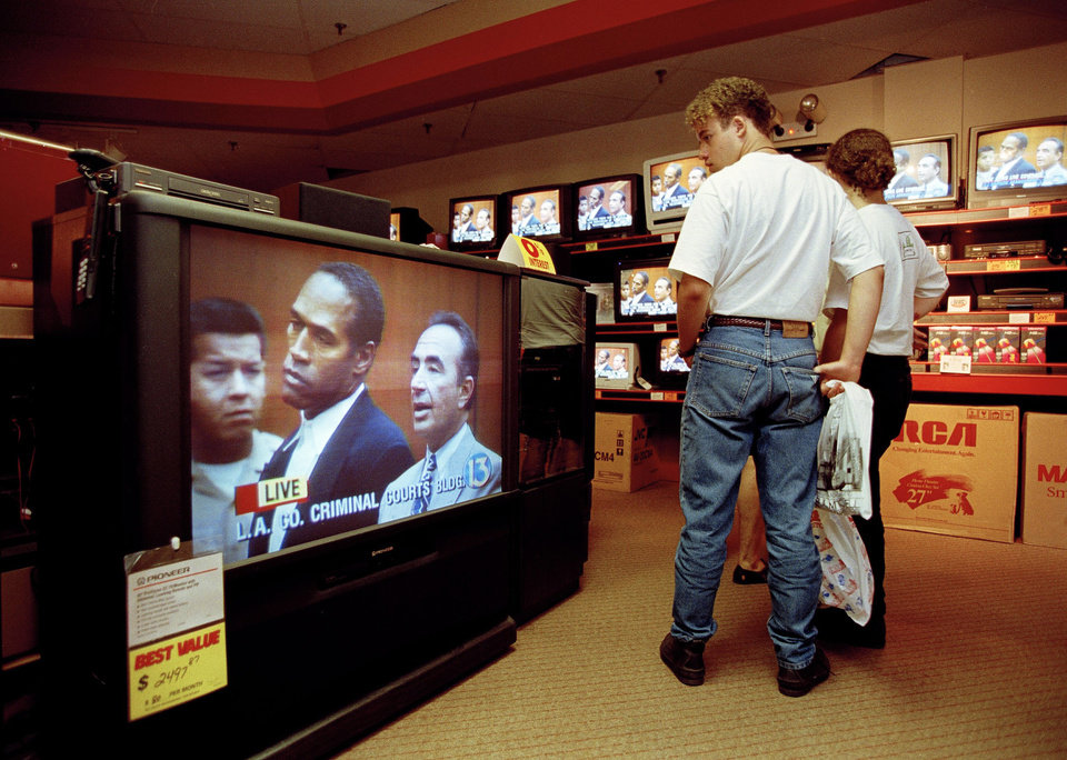 Photo - FILE - In this June 20, 1994 file photo, mall shoppers in Tampa, Fla., watch banks of televisions in an electronics store as the arraignment of O.J. Simpson is televised from Los Angeles. The O.J. Simpson trial was labeled the